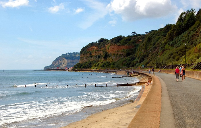 Sandown Beach, people walking along the beach in front of green cliffs ©Ronald Saunders