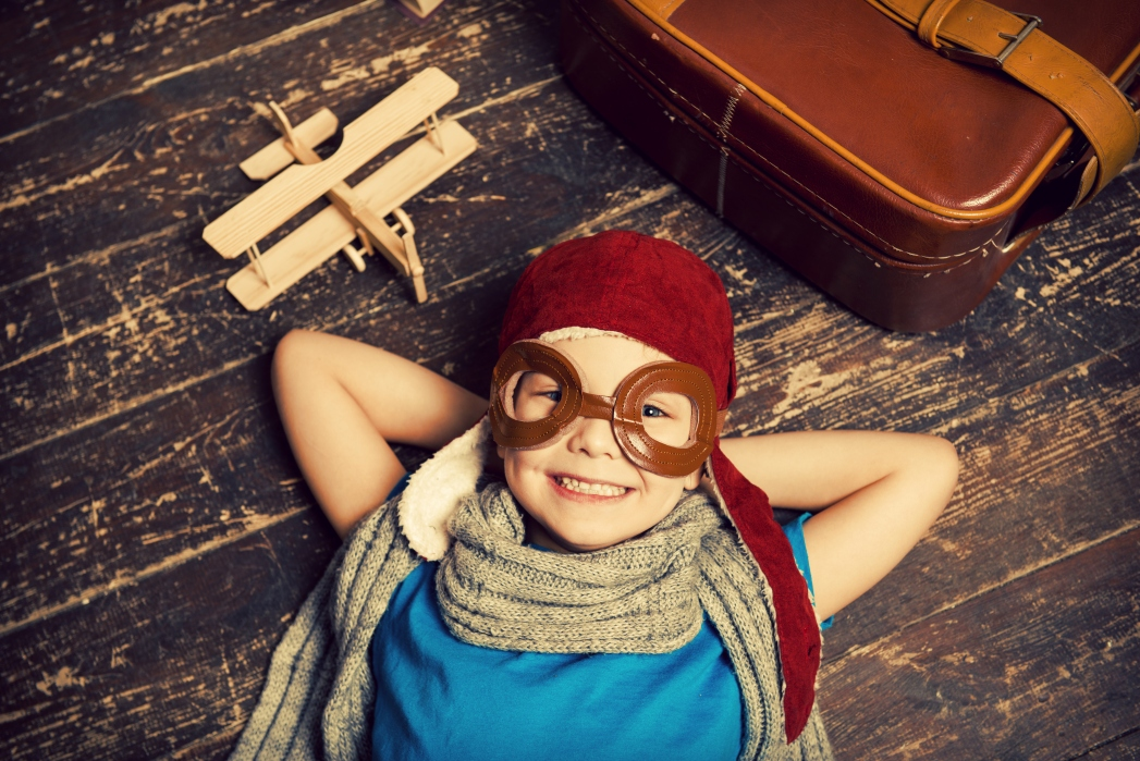 Child in airplane goggles - family packages help you avoid airline charges
