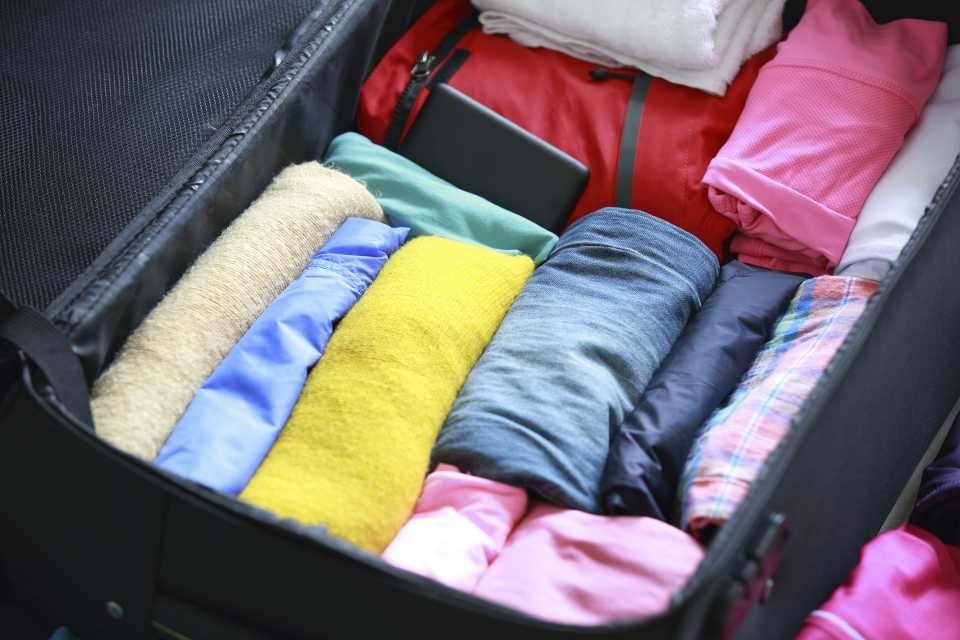 a neat suitcase packed with rolled up clothes