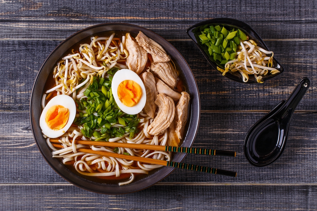 a bowl of noodles with eggs and green vegetables