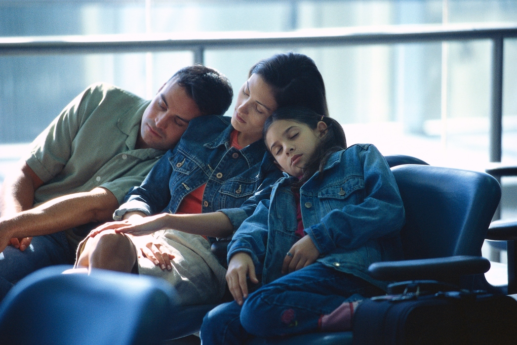 Family sleeping at airport because of flights delays