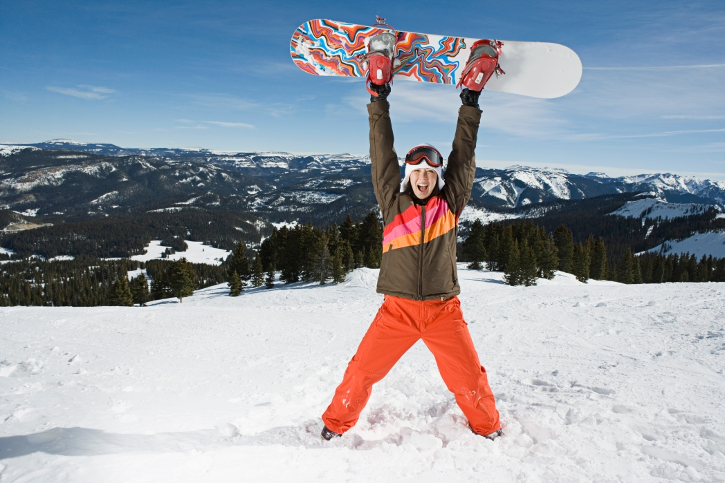 Person standing on a snowy mountain holding a snowboard above their head and smiling