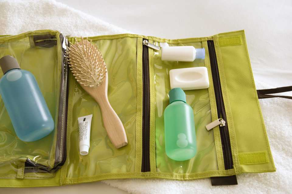 a neatly packed toiletry bag with hairbrush and other products