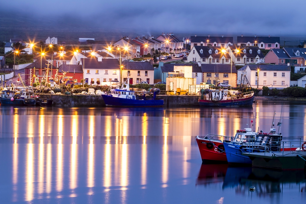 Night view of Portmagee's seafront with light reflections on the water