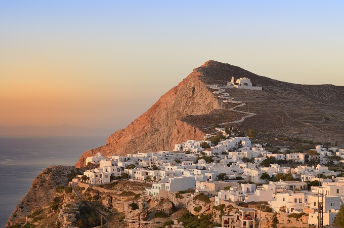 Folegandros, Greece, white buildings leading up the hill, sunset.