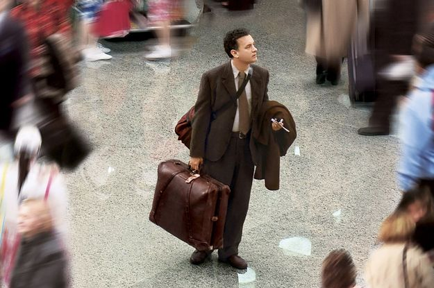 Man Standing in a Busy Airport Looking at the Departure Board with lots of Heavy Bags
