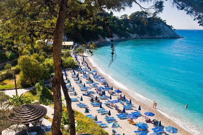 Samos, Greece, sunbeds  with blue umbrellas lined up on a beach.