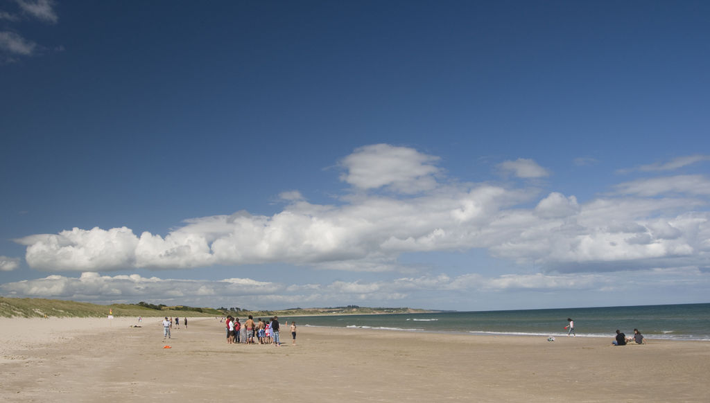 The vast Curracloe Strand, County Wexford under a blue sky with a few clouds. One of the most impressive filming locations in Ireland. Credit: ©Sinead McCarthy / Failte Ireland